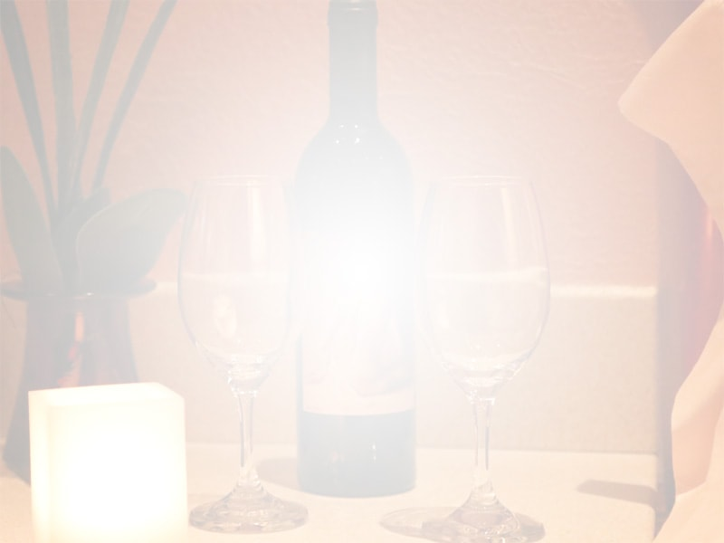 Wine glasses, a bottle of wine, and a lit candle
